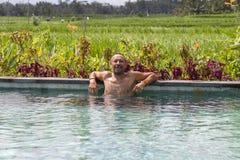 Portret atrakcyjny mężczyzna w pływackim basenie blisko ryż tarasuje na tropikalnej wyspie Bali, Indonezja Obraz Stock
