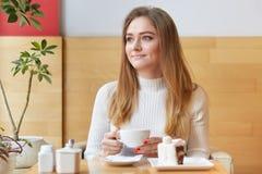 Portret atrakcyjny młody żeński obsiadanie w kawiarni podczas lunchu Urocza blond z włosami dama trzyma filiżankę gorący napój w  zdjęcie stock