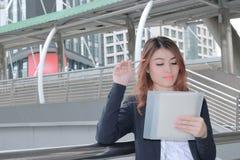 Portret atrakcyjny młody Azjatycki bizneswoman trzyma pióro biznesowymi przy miasta tłem myślących pomysły i Fotografia Royalty Free
