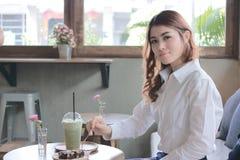 Portret atrakcyjny młody Azjatycki kobiety łasowania punktu deser z rozwidleniem w kawowej kawiarni Zdjęcie Royalty Free