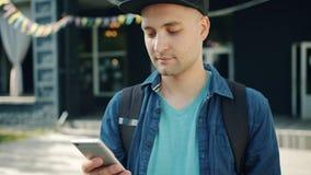 Portret atrakcyjny młody człowiek używa smartphone macania ekran outdoors zbiory