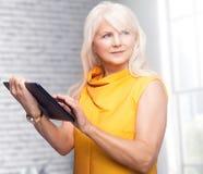 Portret atrakcyjny starszy bizneswoman używa pastylkę fotografia royalty free