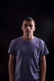 Portret av den allvarliga unga mannen på svart bakgrund i studio Royaltyfri Foto