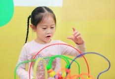 Portret Azjatycka dziecko dziewczyna bawić się edukacyjną zabawkę dla móżdżkowego rozwoju przy dzieciakami izbowymi zdjęcie stock