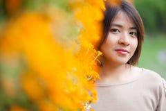 Portret Azjatycka kobieta stoi blisko żółtych kwiatów. fotografia royalty free