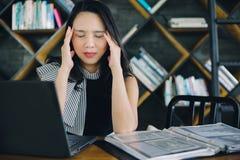 Portret Azjatycka młoda biznesowa dziewczyna pracuje Zapracowanego cierpienie od migreny fotografia royalty free