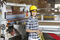 Portret Azjatycki żeński przemysłowy pracownik z mienie drutem z maszynerią w tle Zdjęcie Royalty Free
