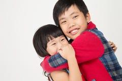 Portret azjatykci śliczny chłopiec uściśnięcie twój siostra z uśmiech twarzą Zdjęcie Royalty Free
