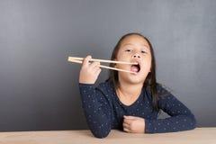 Portret azjatykci małej dziewczynki use chopstick obraz royalty free