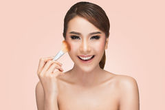 Portret azjatykcia kobieta stosuje suchą kosmetyczną tonalną podstawę na twarzy używać makeup muśnięcie Zdjęcie Stock