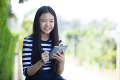 Portret azjatykcia nastoletnia i komputerowa pastylka w ręki use dla cyfry Obrazy Royalty Free
