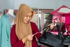 Portret azjatykciego hijab ?e?ski w?a?ciciel i kostiumer pozycja z czarn? kies? w jej butik mody sklepie, m?ody muzu?ma?ski - wiz obrazy stock
