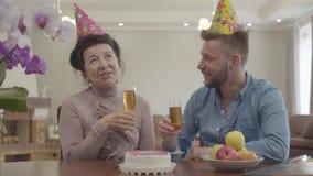 Portret babcia i dorosłego wnuk pije soku obsiadanie przy stołem z urodzinową nakrętką na ich głowach Na stole zbiory wideo