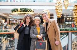 Portret babcia i nastoletni wnuki w centrum handlowym przy bożymi narodzeniami zdjęcie royalty free