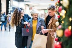 Portret babcia i nastoletni wnuki w centrum handlowym przy bożymi narodzeniami fotografia royalty free