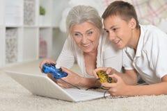 Portret babcia i wnuk bawi? si? gr? komputerow? z laptopem fotografia royalty free