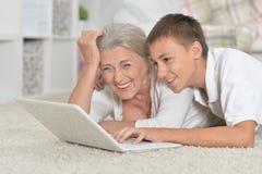 Portret babcia z jej wnukiem u?ywa laptop na dywanie w domu zdjęcie stock
