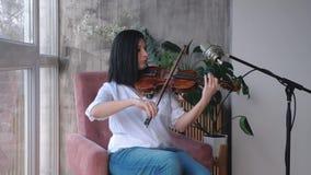 Portret bawić się skrzypce muzyk kobieta, zwolnione tempo zdjęcie wideo