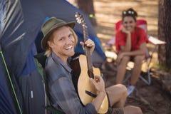 Portret bawić się gitarę uśmiechnięty mężczyzna podczas gdy jego dziewczyny obsiadanie w tle Zdjęcia Royalty Free