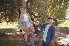 Portret bawić się na drzewnym bagażniku uśmiechnięta para Zdjęcie Royalty Free