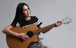 Portret bawić się na gitarze dziewczyna fotografia royalty free
