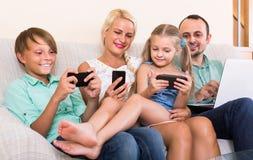 Portret bawić się z gadżetami w domu rodzina Fotografia Stock