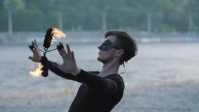 Portret bekwame jonge slanke mens in zwarte kleren en masker die een show met vlam uitvoeren die zich op riverbank bevinden stock videobeelden