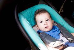 Portret berbeć chłopiec w samochodowym siedzeniu Mały uśmiechnięty dziecka dziecko przymocowywał z pasa bezpieczeństwa portretem  zdjęcie stock