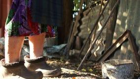 Portret biedne stare starsze osoby przerzedże kobiety w wiosce w wschodnim Europe Kobieta stoi blisko narzędzi - stary pitchfork zbiory wideo