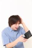 Portret biedny młody Japoński mężczyzna lokking dla jego pustego portfla zdjęcia stock
