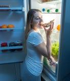 Portret bierze pizza plasterek z chłodziarki i je je głodna młoda kobieta Pojęcie dieting i gubienie Obraz Royalty Free
