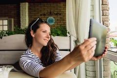 Portret bierze selfie w sklep z kawą uśmiechnięta kobieta używać cyfrową pastylkę Zdjęcie Stock
