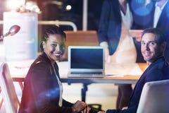 Portret biznesmena i bizneswomanu obsiadanie przy ich biurkiem Zdjęcia Stock