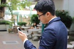 Portret biznesmena mienia mobilny smartphone w parku Fotografia Royalty Free