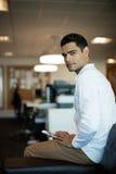 Portret biznesmena mienia telefon komórkowy przy biurem Zdjęcia Stock