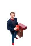 Portret biznesmena obsiadanie na jego walizce podczas gdy i uśmiech Zdjęcia Stock