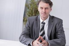 Portret biznesmena obsiadanie przy biurkiem Zdjęcia Stock