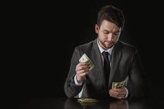 Portret biznesmena obsiadanie przy stołem i odliczającym pieniądze Zdjęcia Stock
