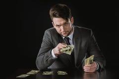 Portret biznesmena obsiadanie przy stołu i mienia pieniądze Zdjęcia Royalty Free