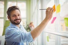 Portret biznesmena writing na adhezyjnych notatkach przy biurem Obraz Royalty Free