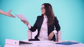 Portret biznesowa kobieta Brunetka w szkłach siedzi w znakach i biurze dokumenty przynoszący pracownikiem zbiory