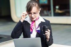 Portret biznesowa kobieta siedzi w mieście i patrzeje laptop zaskakująco w szkłach Obraz Royalty Free