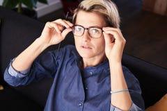 Portret biznesowa kobieta siedzi z krótkiego włosy spojrzeniami kamera w szkła przy nowożytnym mieszkaniem Światło dzienne obraz stock