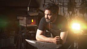 Portret blacksmith w pracującej atmosferze Mężczyzna pracuje z stopionym metalem w kuźni Obraz Stock