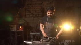 Portret blacksmith w pracującej atmosferze Mężczyzna pracuje z stopionym metalem w kuźni Zdjęcie Stock