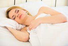 Portret blond dziewczyna z długie włosy dosypianiem w łóżku obrazy royalty free