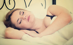 Portret blond dziewczyna z długie włosy dosypianiem w łóżku