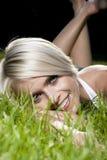 Portret blond kobieta kłaść w trawie Zdjęcia Royalty Free