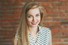 Portret blondynka w świetle Stojący przeciw czerwonemu ściana z cegieł tłu, ono uśmiecha się i pozujący dla kamery, jej długie wł Obraz Stock