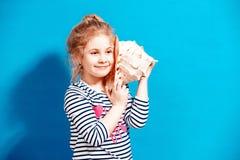 Portret blondynki dziecka dziewczyna słucha seashell przy błękitną ścianą Zdjęcia Stock
